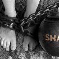 image of a person shackled with a shame ball